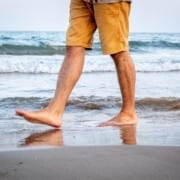 man walking on beach showing only legs