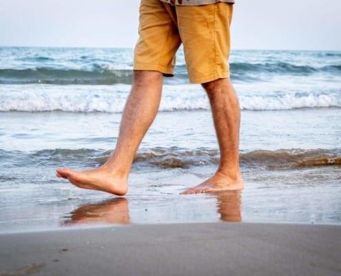 man walking on beach showing only legs