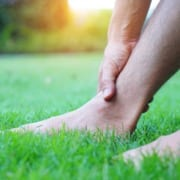 man holding ankle sitting in grass